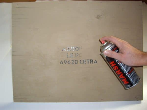 Recouvrement marquage sur caisse en bois avec bombe TMO pour réutilisation. Evite le poncage de la caisse.